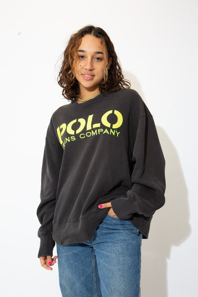 the model wears a faded black sweater with polo jeans company spell out