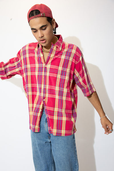 Short-sleeved button-up with an allover pink, yellow, blue and green plaid print across the tee.