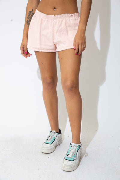 the model wears a pair of pink shorts