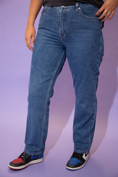 the model wears a dark washed pair of tommy hilfiger jeans