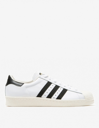 Adidas Superstar 80s Originals • Low top sneaker in White • Leather upper • Suede lateral-side '3-stripes' • Flat cotton laces • Branded tongue logo • Padded collar • Suede insole • Classic rubber shell toe • Branded heel logo • Herringbone-pattern rubber cupsole • Men's sizes listed
