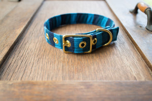 Blue ikat dog collar with brass hardware on a wooden board