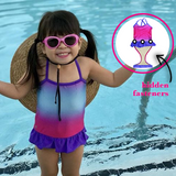 Little girl at pool wearing FASTEN swimsuit, Fuchsia Turquoise Ombre cross-back swimsuit for baby and toddler girls. Features patented design that opens at the waist, making bathroom breaks and baby diaper changes faster and easier. Sizes 6m-5. UPF 50 sun protection built right in! Cross-back swimsuit design. Ombre varies slightly in each swimsuit. Open and secured in back with hidden magnet.