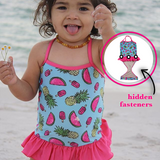 Toddler at beach wearing FASTEN swimsuit, Fruitsicle cross-back swimsuit for baby and toddler girls. Features patented design that opens at the waist, making bathroom breaks and baby diaper changes faster and easier. Sizes 6m-5. UPF 50 sun protection built right in! Cross-back swimsuit design. Cute fruit pattern with ruffle.