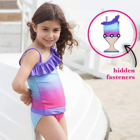 Girl at Beach wearing Fuchsia Turquoise Ombre one-shoulder swimsuit for girls by FASTEN. Features patented design that opens at the waist, making bathroom breaks and baby diaper changes faster and easier. Sizes 2T-10. UPF 50  sun protection built right in! One-shoulder design. Ombre varies slightly in each swimsuit.