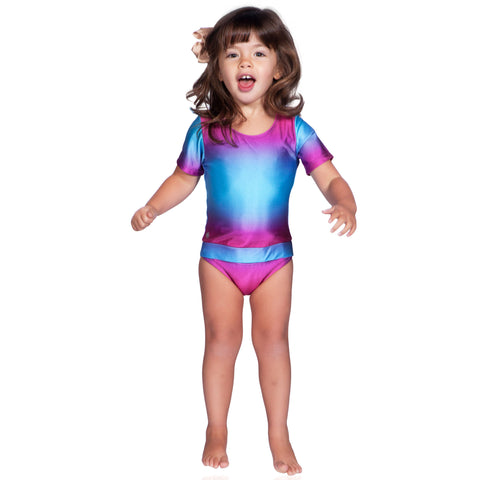 Fuchsia Turquoise Ombre short sleeve swimsuit by FASTEN. Rash guard swimsuit. Fits toddler girls and young girls, sizes 2T-10. Features patented design that opens at the waist, making bathroom breaks and baby diaper changes faster and easier. UPF 50 sun protection built right in! Ombre varies slightly in each swimsuit.