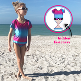 Young girl at beach wearing Fuchsia Turquoise Ombre short sleeve swimsuit by FASTEN. Rash guard swimsuit. Fits toddler girls and young girls, sizes 2T-10. Features patented design that opens at the waist, making bathroom breaks and baby diaper changes faster and easier. UPF 50 sun protection built right in! Ombre varies slightly in each swimsuit.
