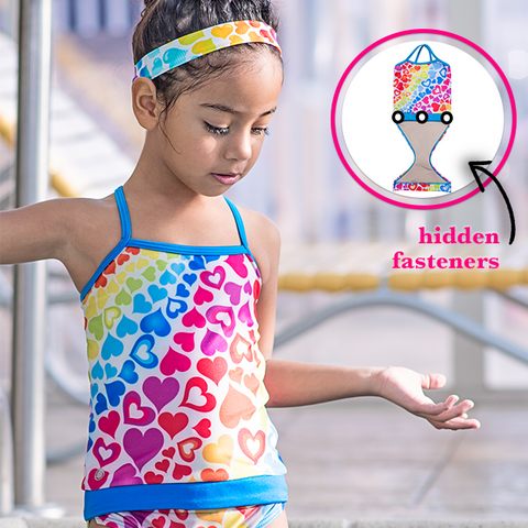 Young girl at pool wearing FASTEN rainbow hearts swimsuit for girls. Sizes 6m - 5. UPF 50 sun protection. Patented design that opens at the waist, making diaper changes and bathroom breaks faster and easier. Perfect for potty training! Cross-back design with hearts pattern.