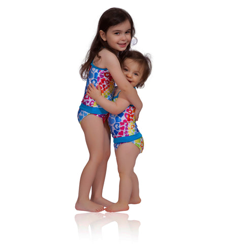 FASTEN rainbow hearts swimsuit for girls. Big sis and little sis! Sizes 6m - 5. UPF 50 sun protection. Patented design that opens at the waist, making diaper changes and bathroom breaks faster and easier. Perfect for potty training! Cross-back design with hearts pattern.