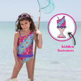 Girl at beach wearing Summer Emoji one-shoulder swimsuit for girls by FASTEN. Features patented design that opens at the waist, making bathroom breaks faster and easier. Sizes 2T-10. UPF 50 sun protection built right in! One-shoulder design. Cute emoji pattern!