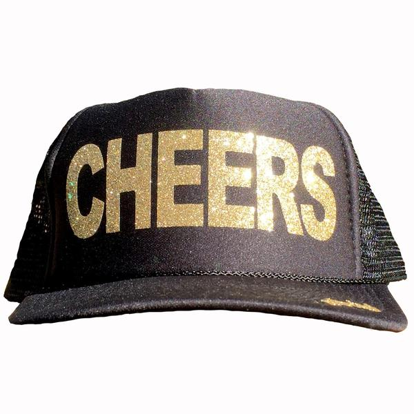 Cheers in glitter gold ink on the front panel of a black mesh trucker cap with an adjustable snapback