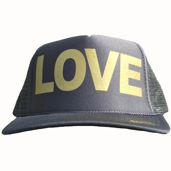 LOVE in gold ink on the front panel of a classic mesh charcoal trucker cap with an adjustable snapback