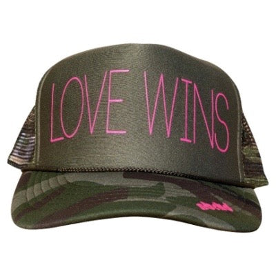 Love Wins in pink ink on the front panel of a classic mesh camo trucker cap with an adjustable snapback