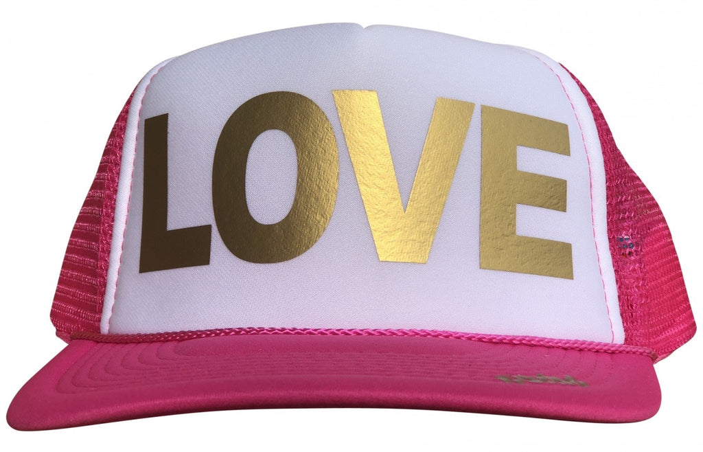 LOVE in gold ink on the front panel of a classic mesh pink-white trucker cap with an adjustable snapback