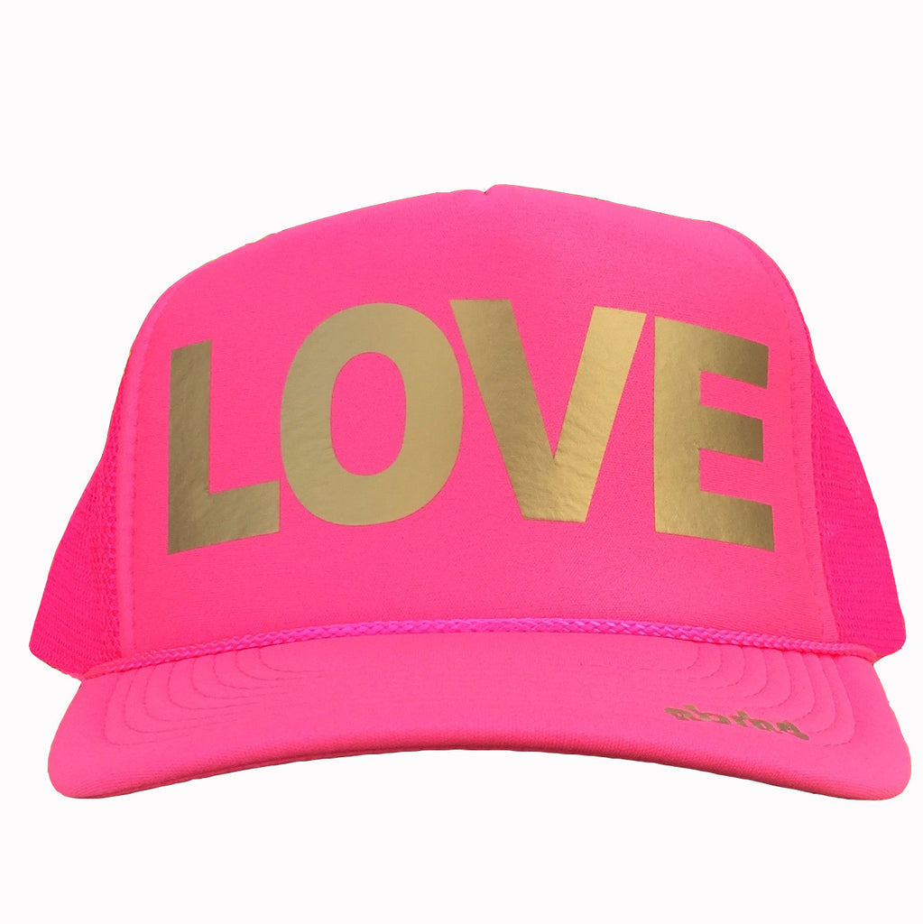 LOVE in gold ink on the front panel of a classic mesh pink trucker cap with an adjustable snapback