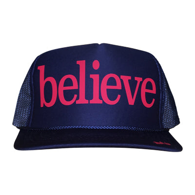 Believe in pink ink on the front panel of a classic mesh navy trucker cap with an adjustable snapback