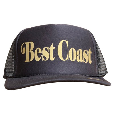 Best Coast in gold ink on the front panel of a classic mesh black trucker cap with an adjustable snapback
