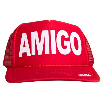 Amigo in white ink on the front panel of a classic mesh red trucker cap with an adjustable snapback