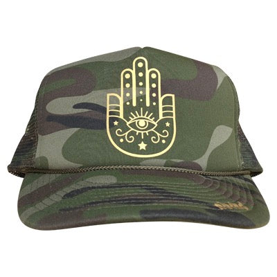 Hamsa Hand graphic in gold ink on the front panel of an olive camo trucker cap with an adjustable snapback