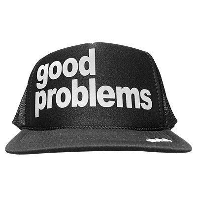 Good problems in white ink on the front panel of a black mesh trucker cap with an adjustable snapback