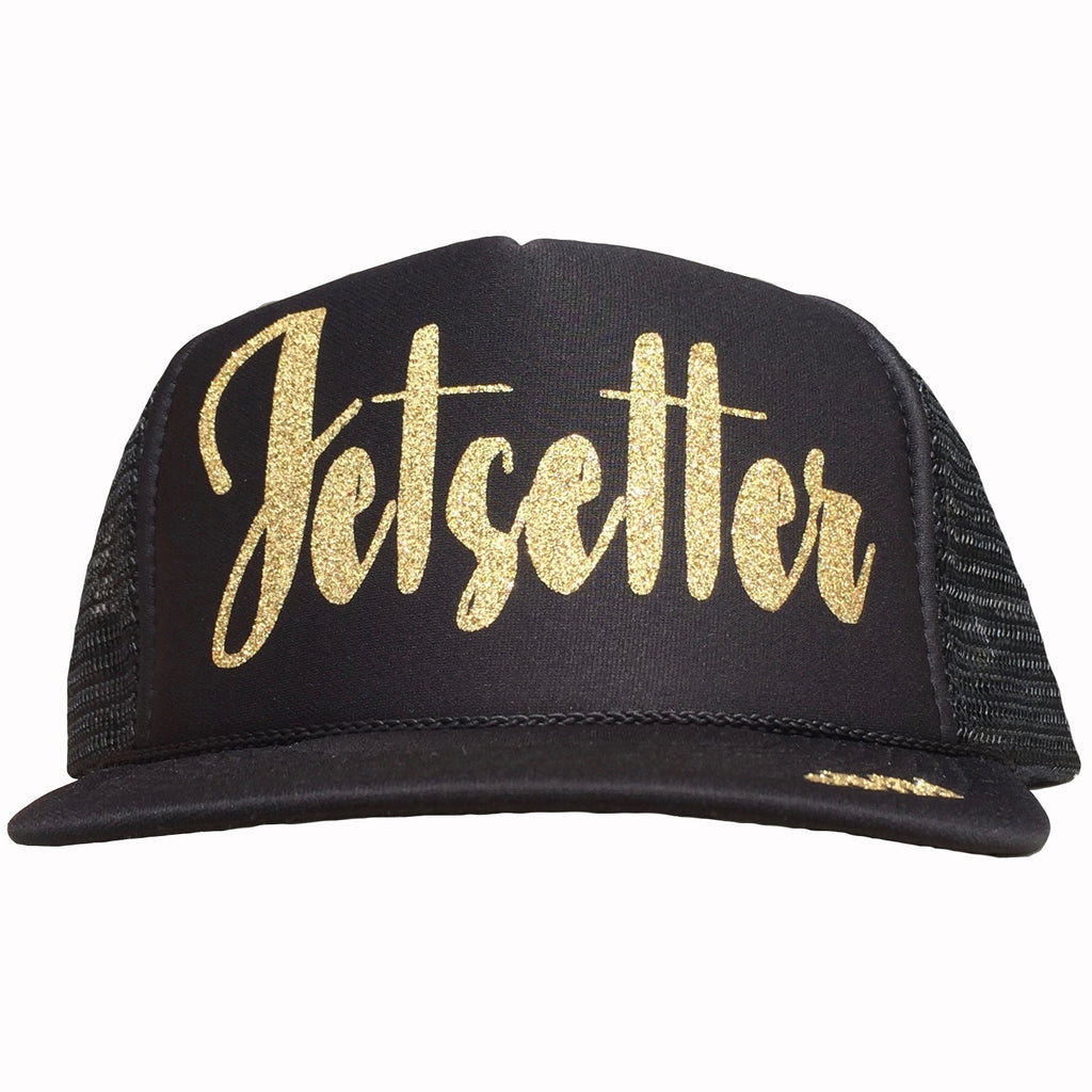Jetsetter in glitter gold ink on the front panel of a black trucker cap with an adjustable snapback