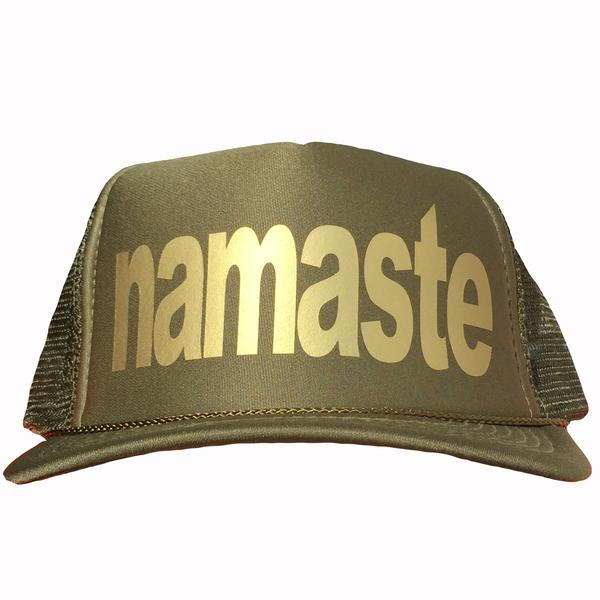 Namaste in gold ink on the front panel of a classic mesh olive trucker cap with an adjustable snapback