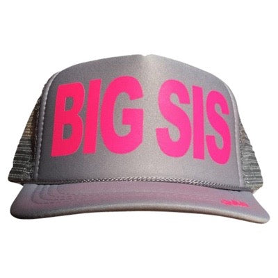 Big Sis in pink ink on the front panel of a kid's mesh light gray trucker cap with an adjustable snapback, small fit