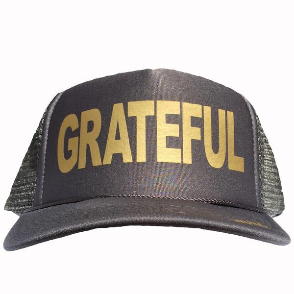 Grateful in gold ink on the front panel of a charcoal mesh trucker cap with an adjustable snapback