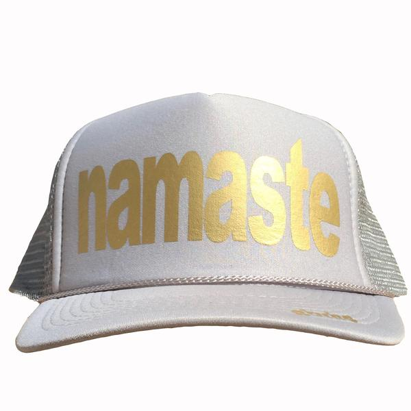 Namaste in gold ink on the front panel of a classic mesh gray trucker cap with an adjustable snapback