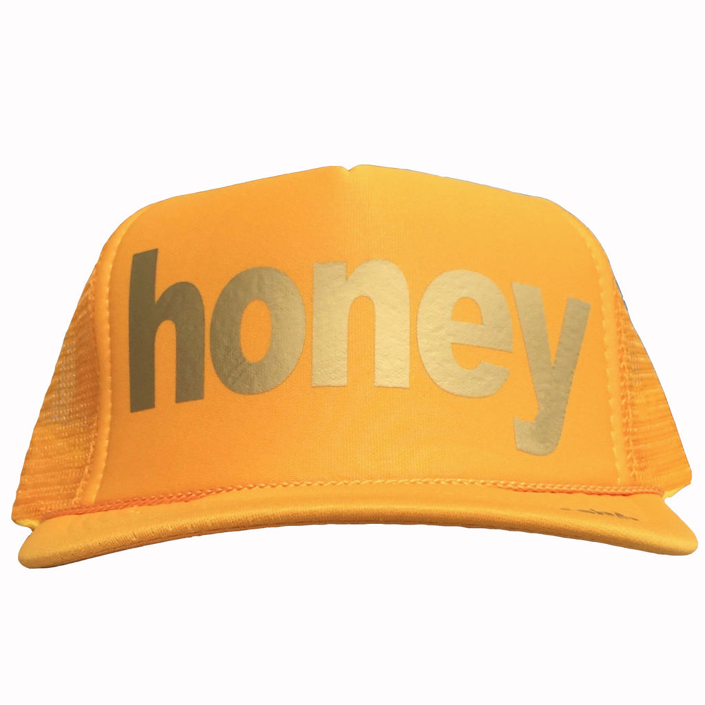 Honey in gold ink on the front panel of a yellow mesh trucker cap with an adjustable snapback