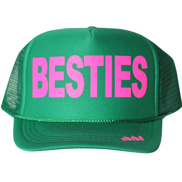Kid's Besties in neon pink ink on the front panel of a classic mesh green trucker cap with an adjustable snapback