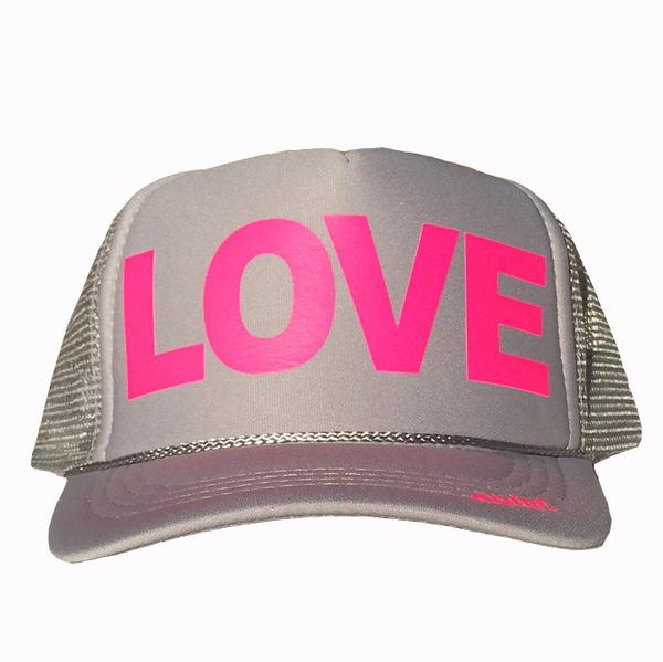 LOVE in hot pink ink on the front panel of a classic mesh gray trucker cap with an adjustable snapback