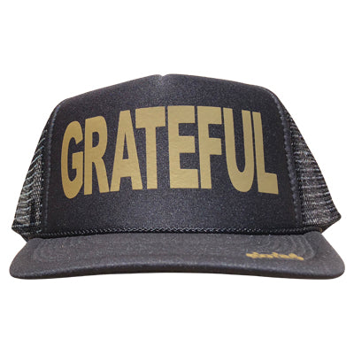 Grateful in gold ink on the front panel of a black mesh trucker cap with an adjustable snapback