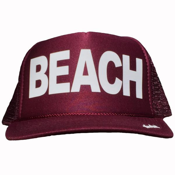 BEACH in white ink on the front panel of a classic mesh maroon trucker cap with an adjustable snapback