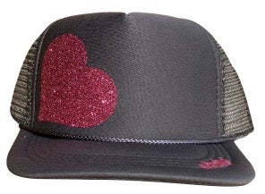 Heart in glitter pink ink on the front panel of a charcoal mesh trucker cap with an adjustable snapback, small fit