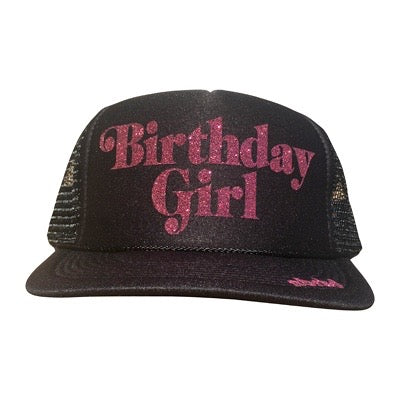Birthday Girl in glitter pink ink on the front panel of a black trucker cap with an adjustable snapback