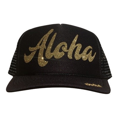 Aloha in glitter gold ink on the front panel of a classic mesh black trucker cap with an adjustable snapback