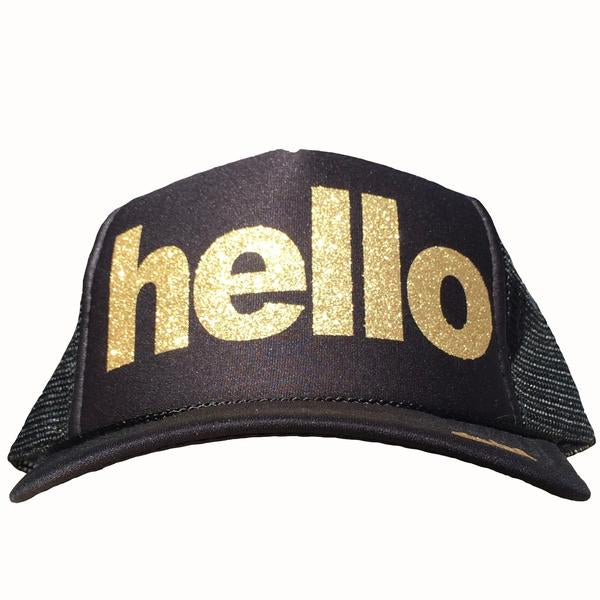 Hello in glitter gold ink on the front panel of a black mesh trucker cap with an adjustable snapback