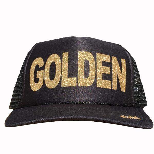 Golden in glitter gold ink on the front panel of a black mesh trucker cap with an adjustable snapback