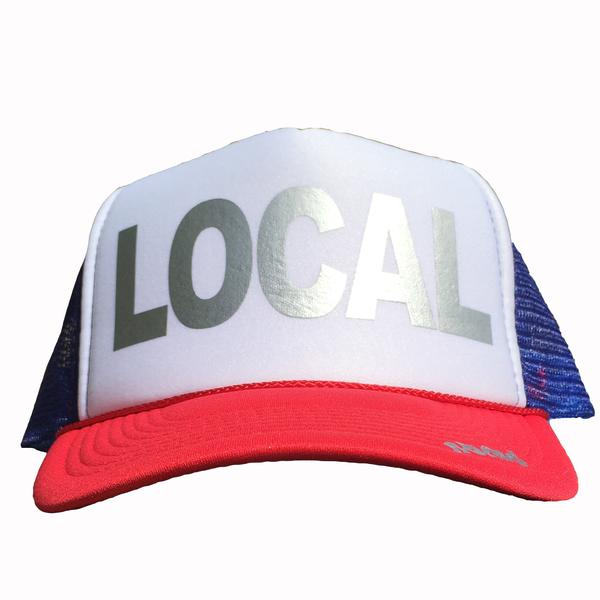 Local in silver ink on the front panel of a red-white-royal trucker cap with an adjustable snapback