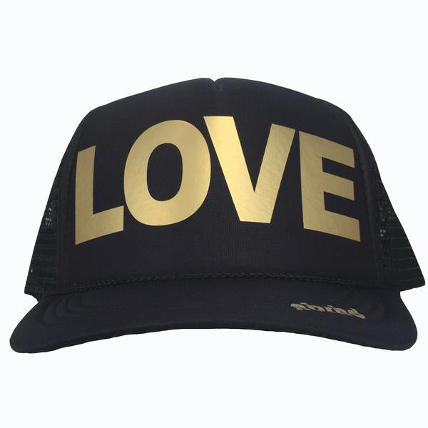 LOVE in gold ink on the front panel of a classic mesh black trucker cap with an adjustable snapback
