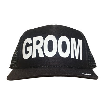 Groom in white ink on the front panel of a black mesh trucker cap with an adjustable snapback