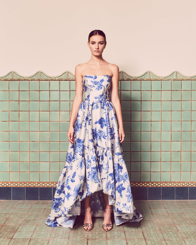 Woman stands while wearing perfect dress for any formal occasion with blue and white floral woven pattern.