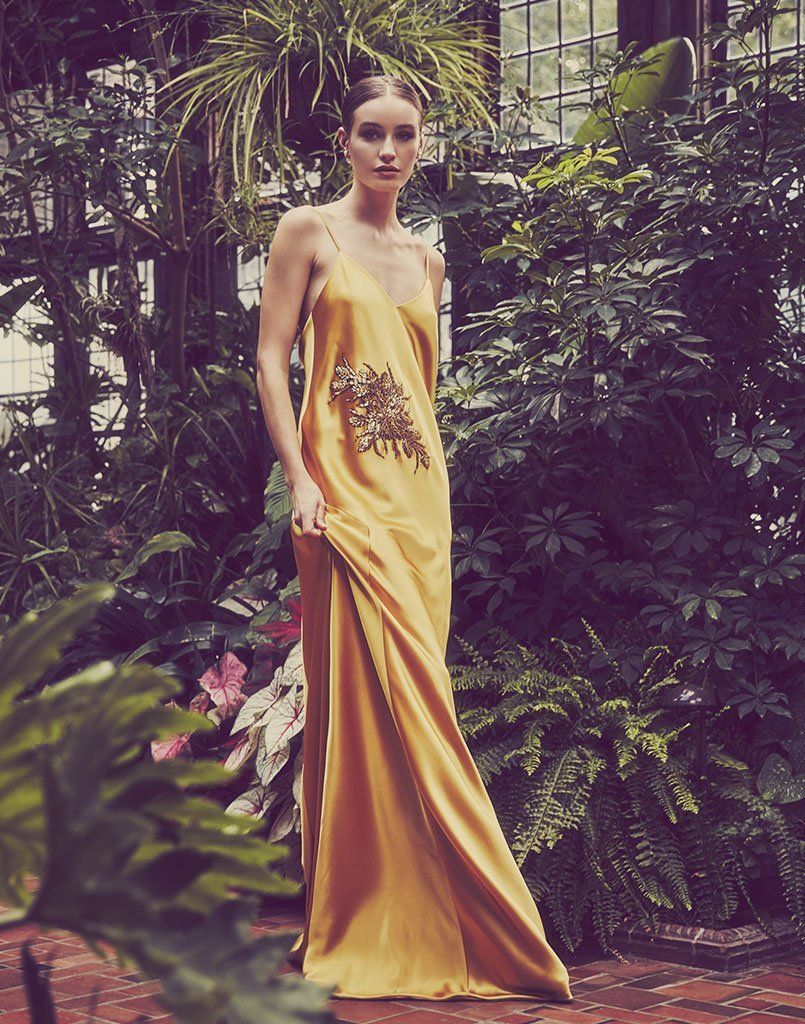 Model standing in green house wears bright yellow slip dress perfect for summer occasions.