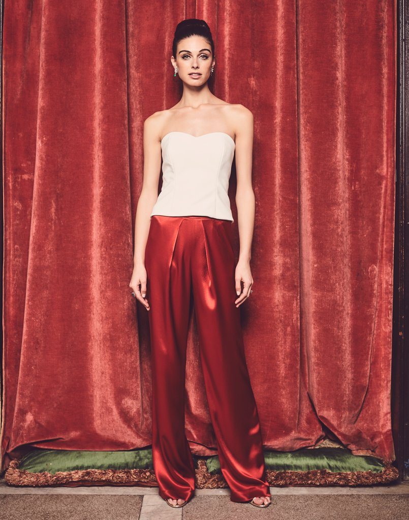 Model against red backdrop wearing white glamorous bustier and red pants