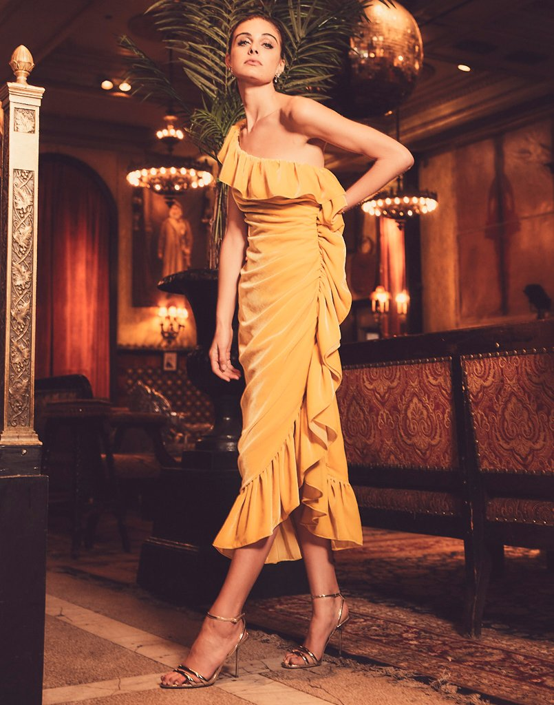 Glamorous woman stands in perfect bright yellow dress ready for cocktails