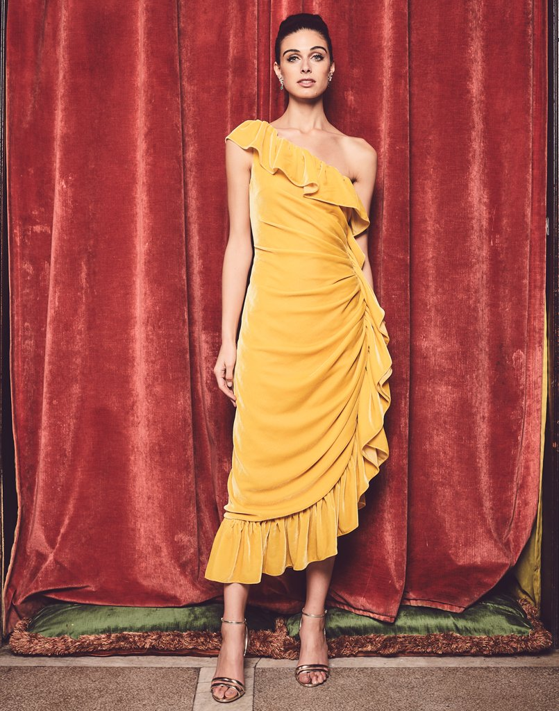 Elegant model wears yellow midi length gown with fluttering ruffles