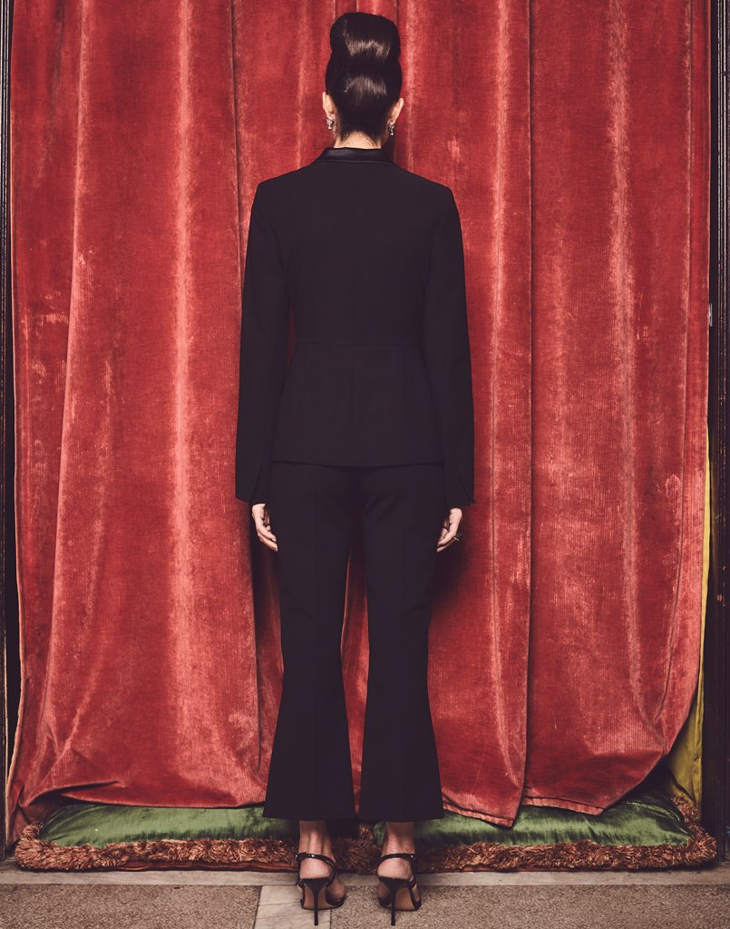 Back view of model wearing a black statement tuxedo jacket