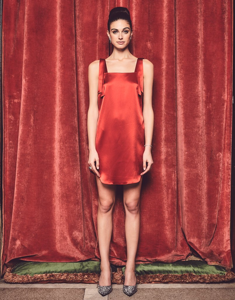 Model against red backdrop wearing a stunning tank dress