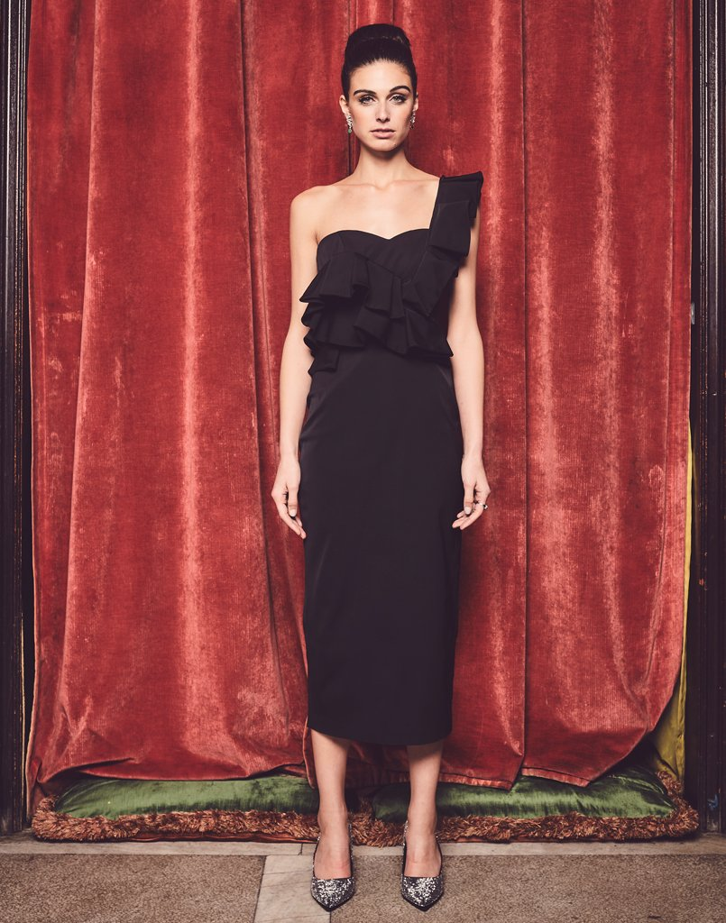 Model against red backdrop wearing a black one shoulder ruffle dress